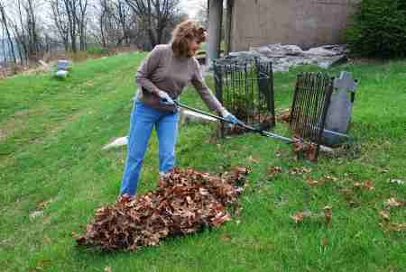Jeanne Remmell rakes leaves to clear gravestones. (Photo Courtesy of Dana Grubb)