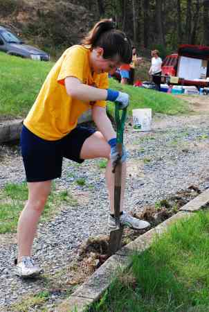 Volunteer Zoe restores a clean edge to an overgrown walkway. (Photo Courtesy of Dana Grubb)