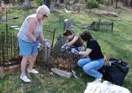 Volunteers clear weeds from an historic headstone (Photo courtesy of Dana Grubb).